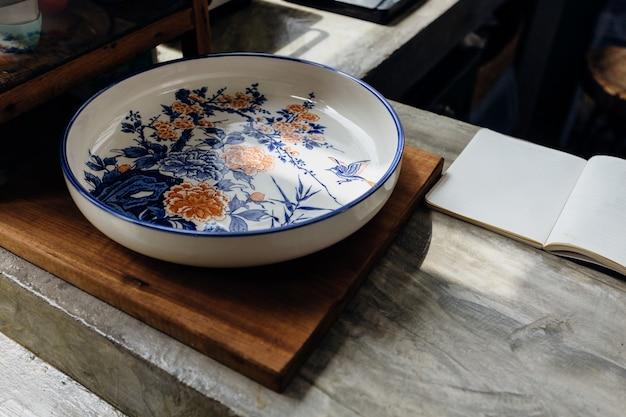 Chinesische traditionelle dekorative keramische platte auf holzklotz mit offenem notizbuch auf küchenarbeitsplatte. Premium Fotos