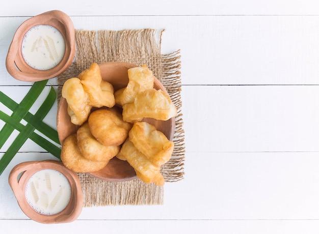 Chinesischer gebratener teig oder youtiao und sojamilch mit hölzernem hintergrund für thailändisches frühstück. thailändisches lebensmittelkonzept. Premium Fotos