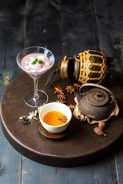 Chinesischer tee, garniert mit sternanis, serviert mit brombeerpudding Kostenlose Fotos