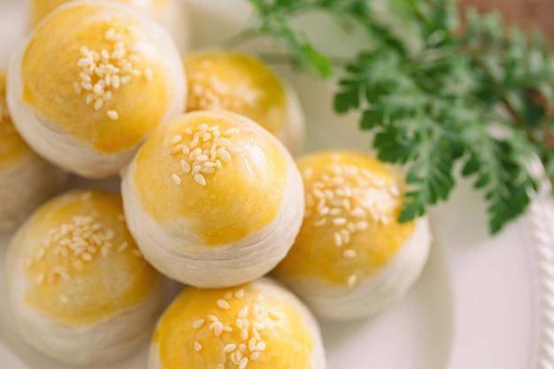 Chinesisches blätterteig oder mooncake füllten süße mungobohnenpaste und gesalzenes eigelb auf weißer platte Premium Fotos