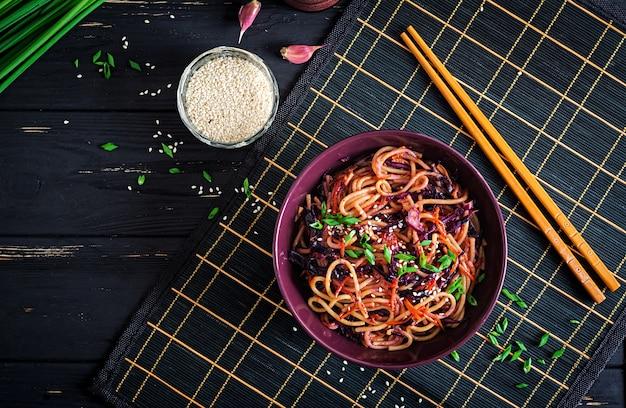 Chinesisches essen. stirfischrogennudeln des strengen vegetariers mit rotkohl und karotte in einer schüssel auf einem schwarzen hölzernen hintergrund. asiatische küche mahlzeit. ansicht von oben Premium Fotos