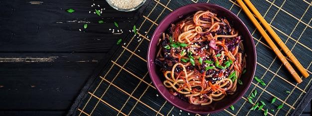 Chinesisches essen. stirfischrogennudeln des strengen vegetariers mit rotkohl und karotte in einer schüssel auf einem schwarzen hölzernen hintergrund. asiatische küche mahlzeit. banner. ansicht von oben Premium Fotos