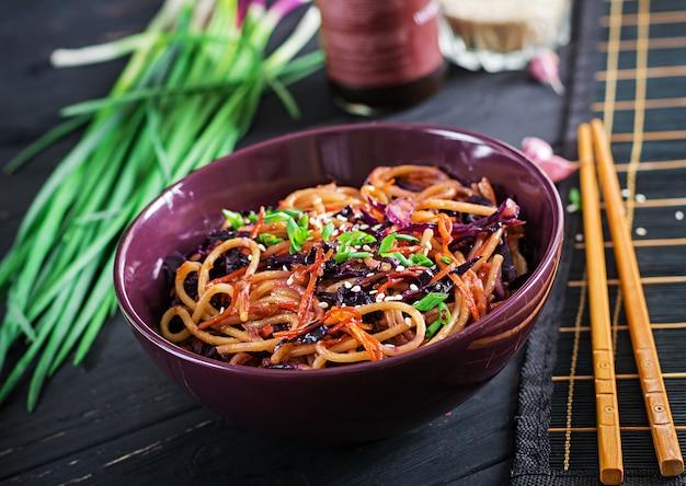 Chinesisches essen. stirfischrogennudeln des strengen vegetariers mit rotkohl und karotte in einer schüssel auf einem schwarzen hölzernen hintergrund. Premium Fotos
