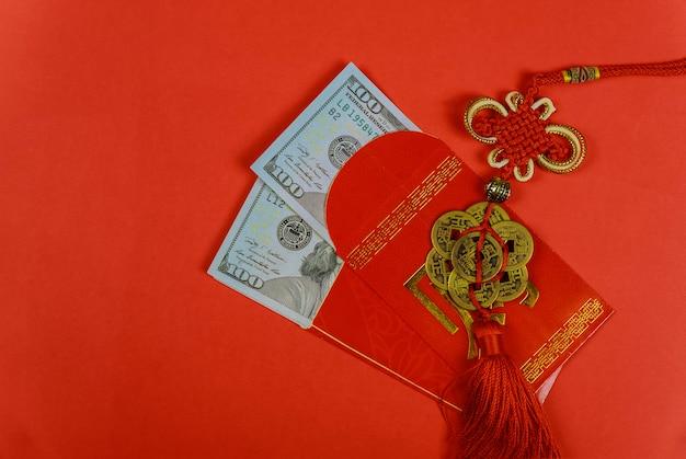 Chinesisches grußgeschenk des neuen jahres, oben geschlossen von den us-dollar banknoten in den roten traditionellen umschlägen Premium Fotos