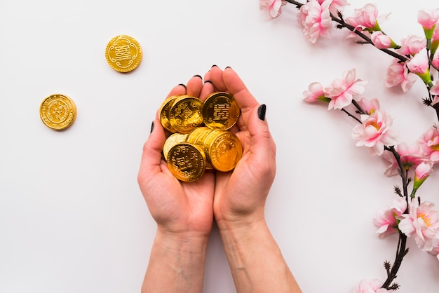 Chinesisches konzept des neuen jahres mit den händen, die münzen halten Kostenlose Fotos