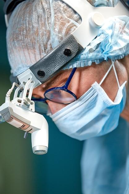 Chirurg arzt mit schutzmaske und hut während des betriebs Premium Fotos