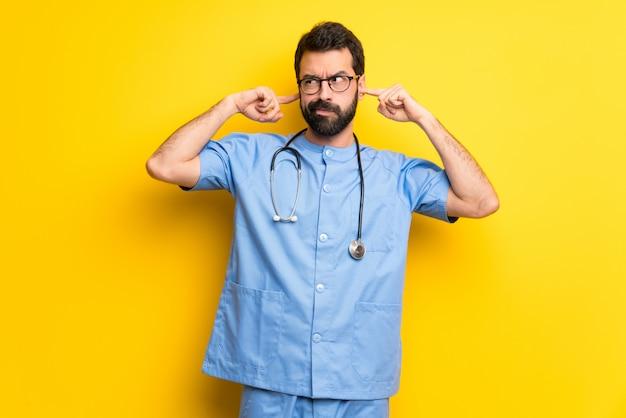 Chirurgdoktormann, der beide ohren mit den händen bedeckt Premium Fotos