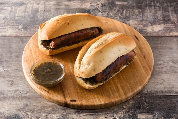 Choripan. traditionelles argentinien-sandwich mit chorizo und chimichurri sauce auf holztisch Premium Fotos
