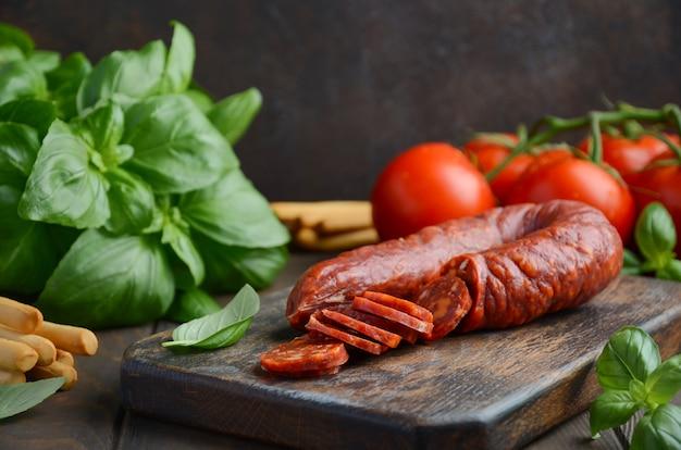 Chorizo-wurst. spanische traditionelle chorizo-wurst mit frischen kräutern und tomaten. Premium Fotos