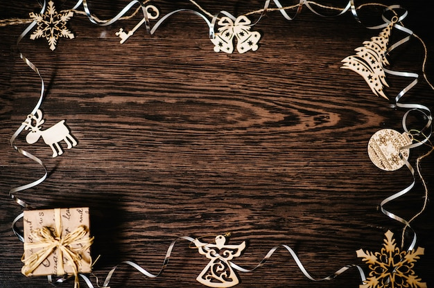 Christbaumschmuck, geschenk, schachtel mit bändern, schneeflocken, glocken, hirsch, engel auf einem braunen, strukturellen holzhintergrund. flach liegen. draufsicht, rahmen mit platz für text. schöne ferien. Premium Fotos