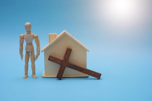 Christliches konzept mit holzkreuz, holzhaus und holzleuten. Premium Fotos