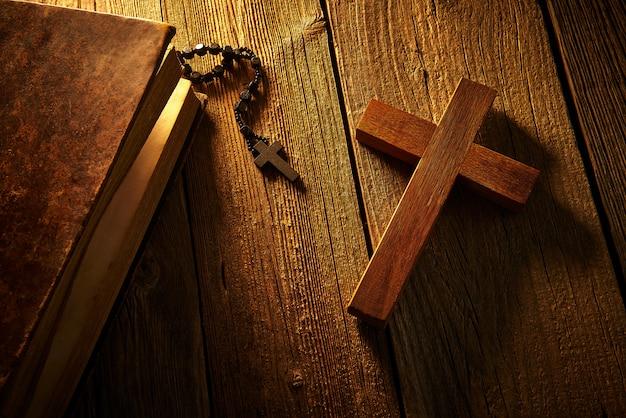 Christliches kreuz auf hölzerner bibel und rosenbeet Premium Fotos