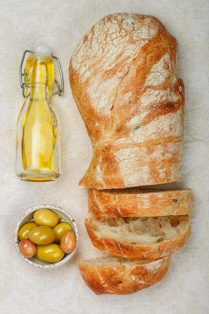 Ciabatta mit oliven, frischem köstlichem traditionellem italienischem geschnittenem brot, oliven und olivenöl auf einem weißen holztisch Premium Fotos