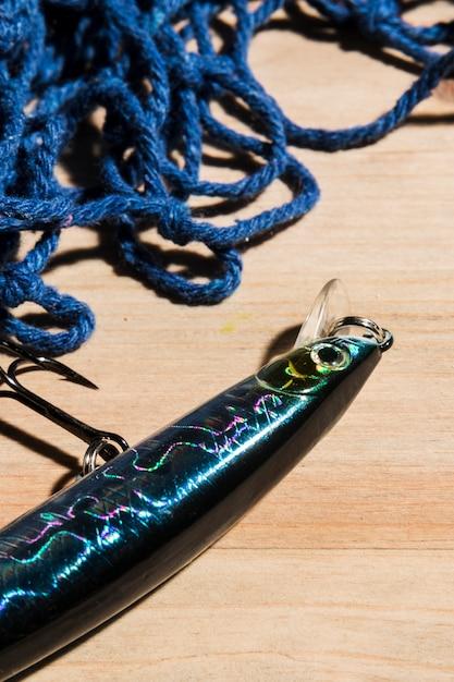 Cloe-up des fischköders mit haken und fischernetz auf holzoberfläche Kostenlose Fotos