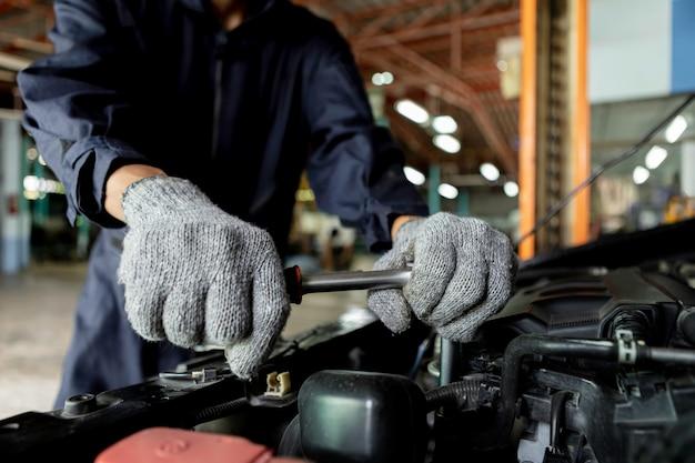 Close up, automechaniker die leute reparieren ein auto verwenden sie einen schraubenschlüssel und einen schraubendreher, um zu arbeiten. reparaturdienst. authentische nahaufnahme. Premium Fotos