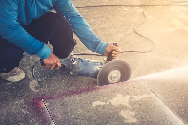 Close up hand mann schneiden betonboden mit maschine. Premium Fotos