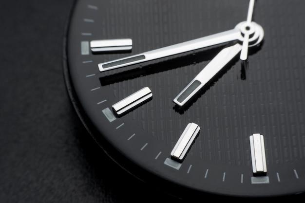 Close up im uhrzeigersinn auf schwarzem zifferblatt hintergrund. armbanduhr im retro-stil Premium Fotos
