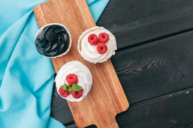 Close up of einige dekadente gourmet-cupcakes mit einer vielzahl von zuckerguss aromen gefrostet Premium Fotos