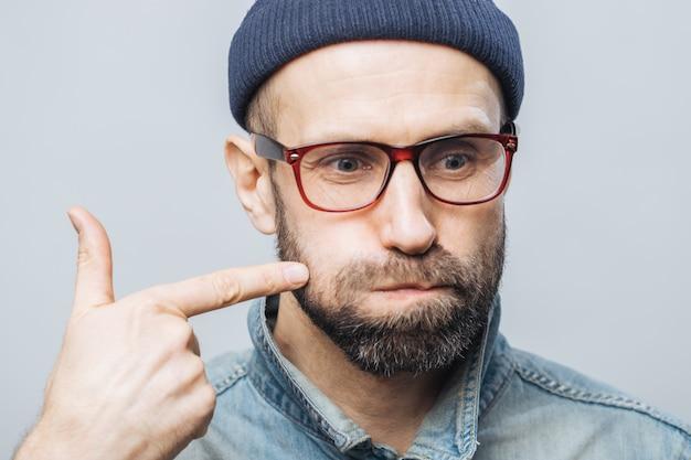 Close up schuss von unrasierten mann mit dicken bart und schnurrbart bläst die wangen und zeigt mit dem zeigefinger Premium Fotos