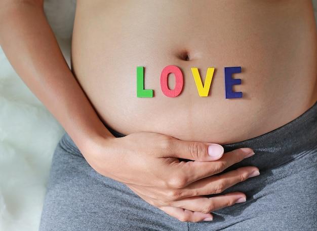 Close up schwangere frau mit liebeswort vor ihrem bauch. Premium Fotos