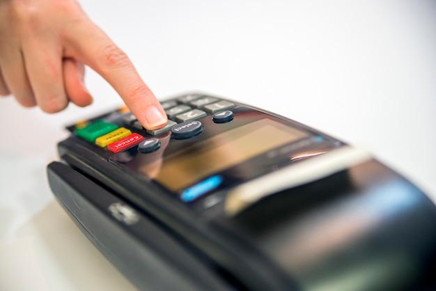 Close-up von karten-service mit pos-terminal, isoliert auf weißem background. weibliche hand mit kreditkarte und bank-terminal Kostenlose Fotos