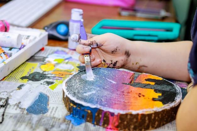 Closeup der holzpalette mit acrylfarbe und pinsel in künstlerhänden auf holz Premium Fotos