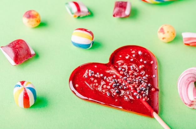 Closuep-aufnahme eines herzförmigen lutschers und anderer süßigkeiten auf einer grünen oberfläche Kostenlose Fotos
