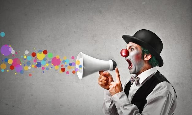 Clown, der in ein megaphon schreit Premium Fotos