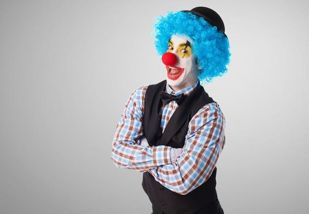 Clown mit den gekreuzten armen machen lustige gesichter Kostenlose Fotos