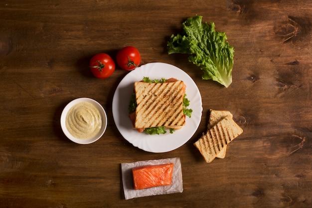 Club sandwich bereitete sich mit fischen auf dem hölzernen brett vor Premium Fotos