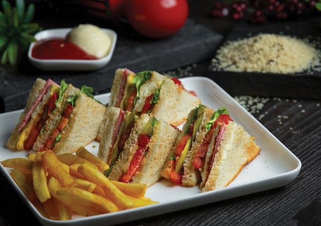 Club sandwich im weißen tablett mit bratkartoffeln. Kostenlose Fotos