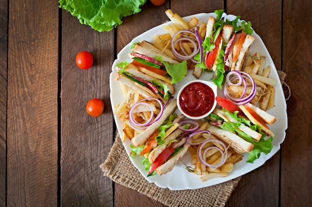 Club sandwich mit käse, gurke, tomate, geräuchertem fleisch und salami. serviert mit pommes frites. Kostenlose Fotos