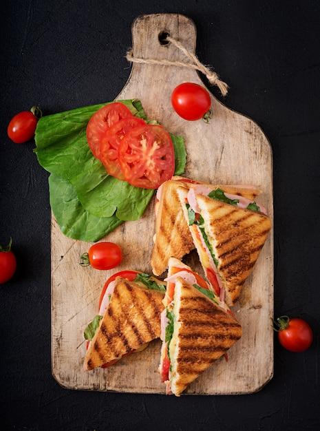 Club sandwich panini mit schinken, tomaten, käse und basilikum. flach legen. draufsicht Premium Fotos