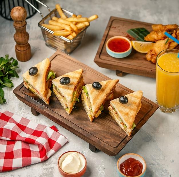 Club sandwiches auf einem holzbrett mit pommes frites und orangensaft. Kostenlose Fotos