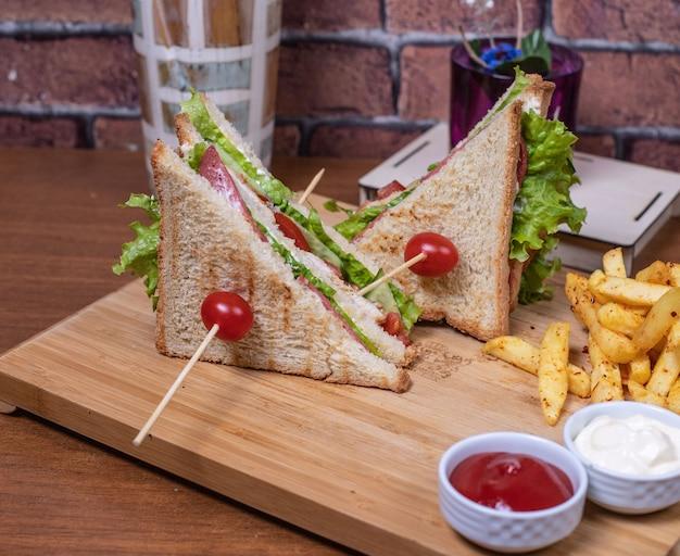 Club sandwiches auf einem holzbrett mit saucen. Kostenlose Fotos