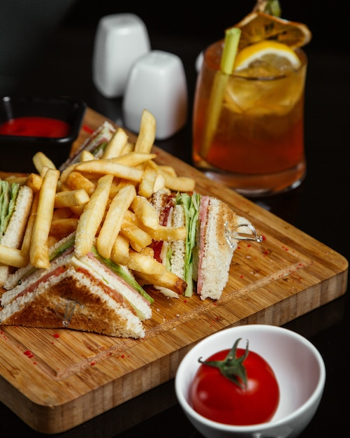 Club sandwiches mit kartoffeln auf einem holzbrett mit tomaten und limonade. Kostenlose Fotos