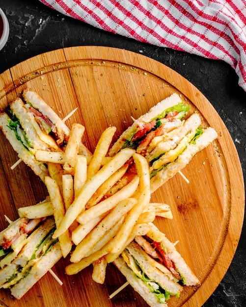 Club sandwiches mit pommes frites auf einem hölzernen runden brett. Kostenlose Fotos