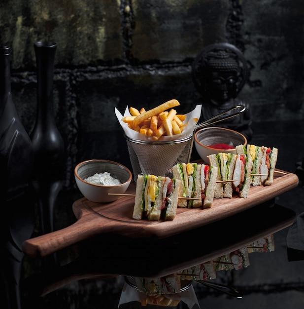 Club sandwiches mit pommes frites in metallischen korb gesetzt Kostenlose Fotos