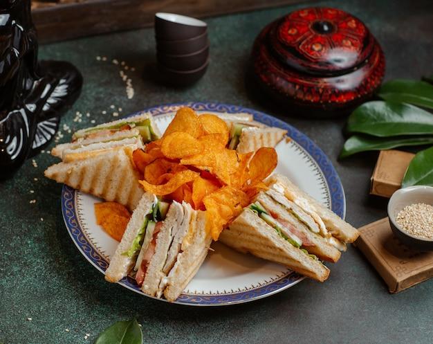 Club sandwiches und kartoffelchips in einer platte. Kostenlose Fotos