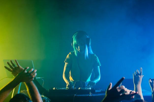 Clubbing mit einer dj-frau, die für die menge mixt Kostenlose Fotos
