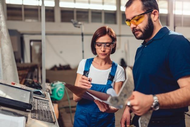 Cnc-maschinenbediener und wirtschaftsingenieur, die produktzeichnung überprüfen Premium Fotos