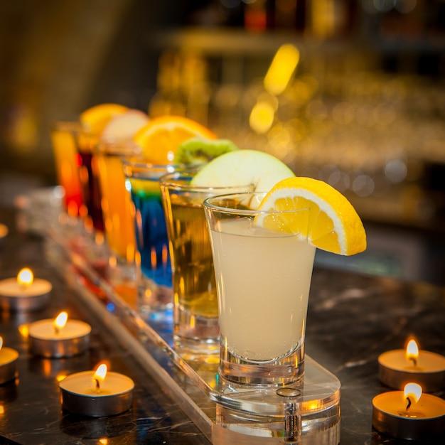 Cocktail-aufnahmen von der seite mit zitronenscheibe, kiwischeibe und kerzen Kostenlose Fotos
