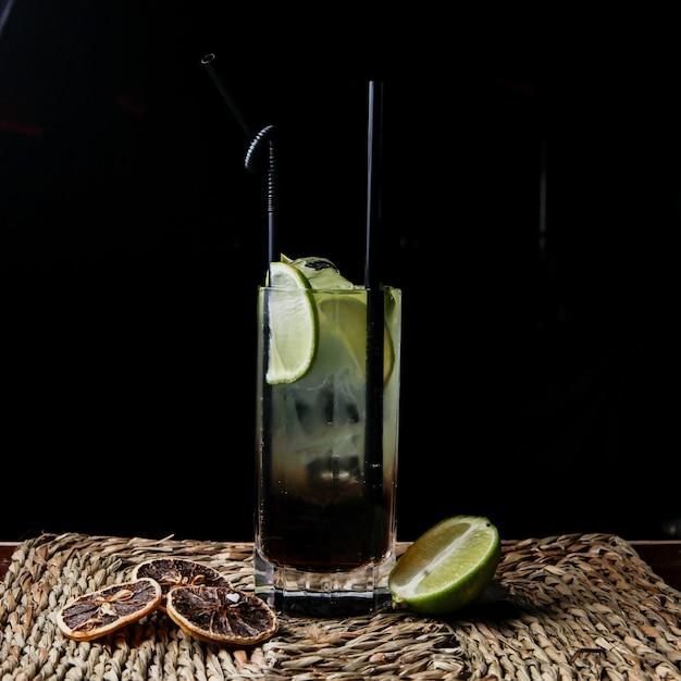 Cocktail kuba pintada von der seite mit tubuli für getränke und getrockneter zitrone und limette in servietten Kostenlose Fotos