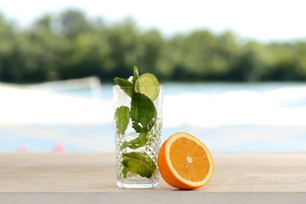 Cocktail mit minze und eis in einem glastrommel. mit blumen- und fruchtdekor Premium Fotos
