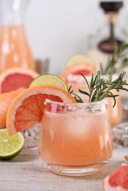 Cocktail pink palomas frische limette und rosmarin kombiniert mit frischem grapefruitsaft und tequila. ein festliches getränk ist ideal für brunch, partys und feiertage. Premium Fotos