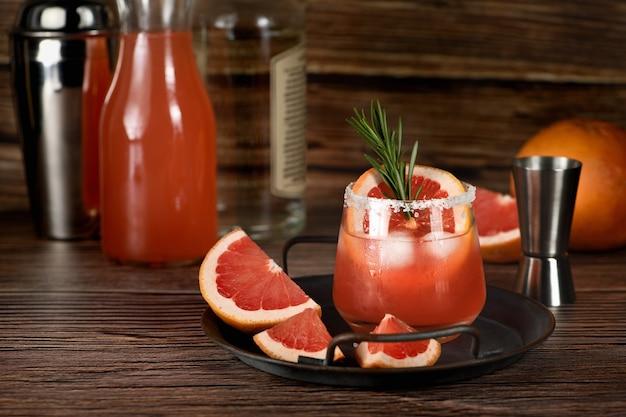 Cocktail tequila frischer grapefruitsaft kombiniert und rosmarin. ein festliches getränk ist ideal für brunch, partys und feiertage. Premium Fotos
