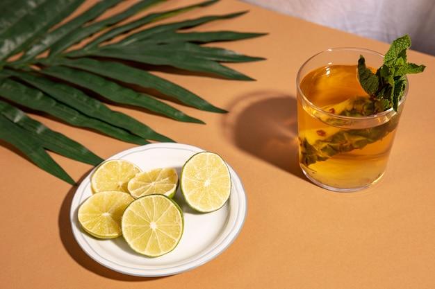 Cocktailgetränk mit zitronenscheiben und palmblatt über braunem schreibtisch Kostenlose Fotos