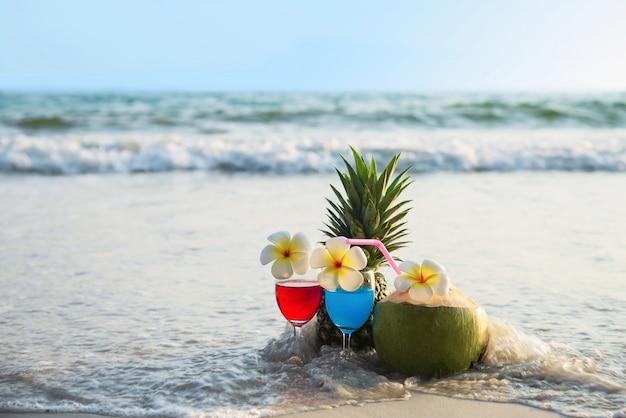 Cocktailgläser mit kokosnuss und ananas auf sauberem sand setzen - frucht und getränk auf seestrand auf den strand Kostenlose Fotos