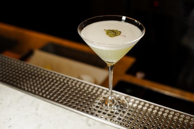 Cocktailglas gefüllt mit dem frischen alkoholischen getränk verziert mit birkenblatt Premium Fotos