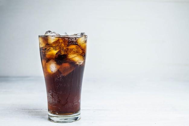 Cola soda in einem glas auf einem weißen tisch Premium Fotos